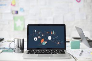 ordinateur portable posé sur un bureau avec graphiques affichés à l'écran