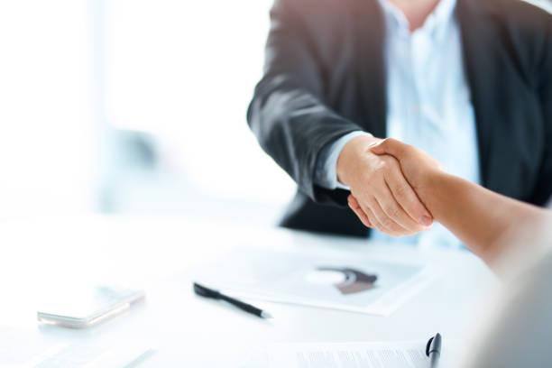 Deux personnes qui se serrent la main par-dessus un bureau