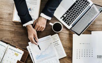personne montrant un document posé sur un bureau à côté d'un ordinateur portable d'un agenda et d'une tasse de café