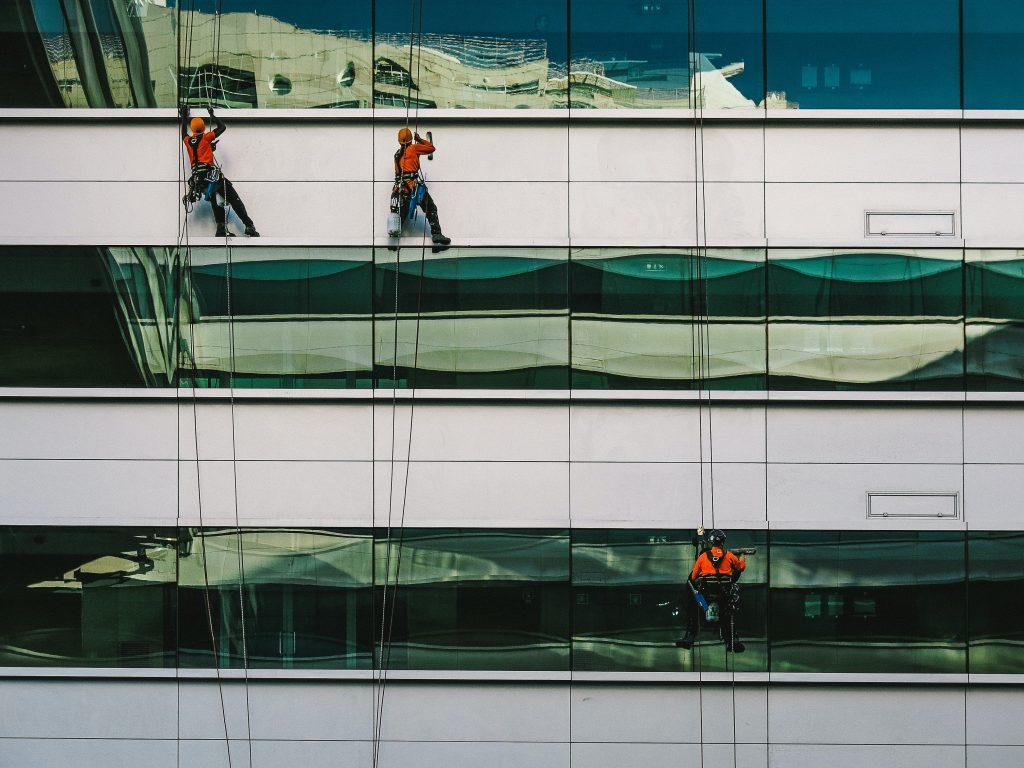 personnes en rappel nettoyant les fenêtres d'un immeuble